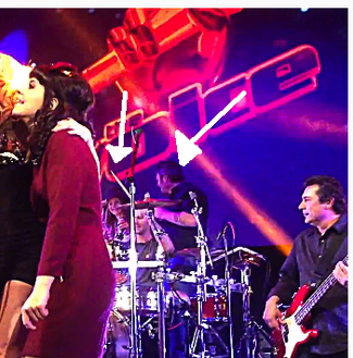Behati stays discreetly aside Adam as he plays drum at The Voice wrap party, here with Blake Shelton on the other side of him